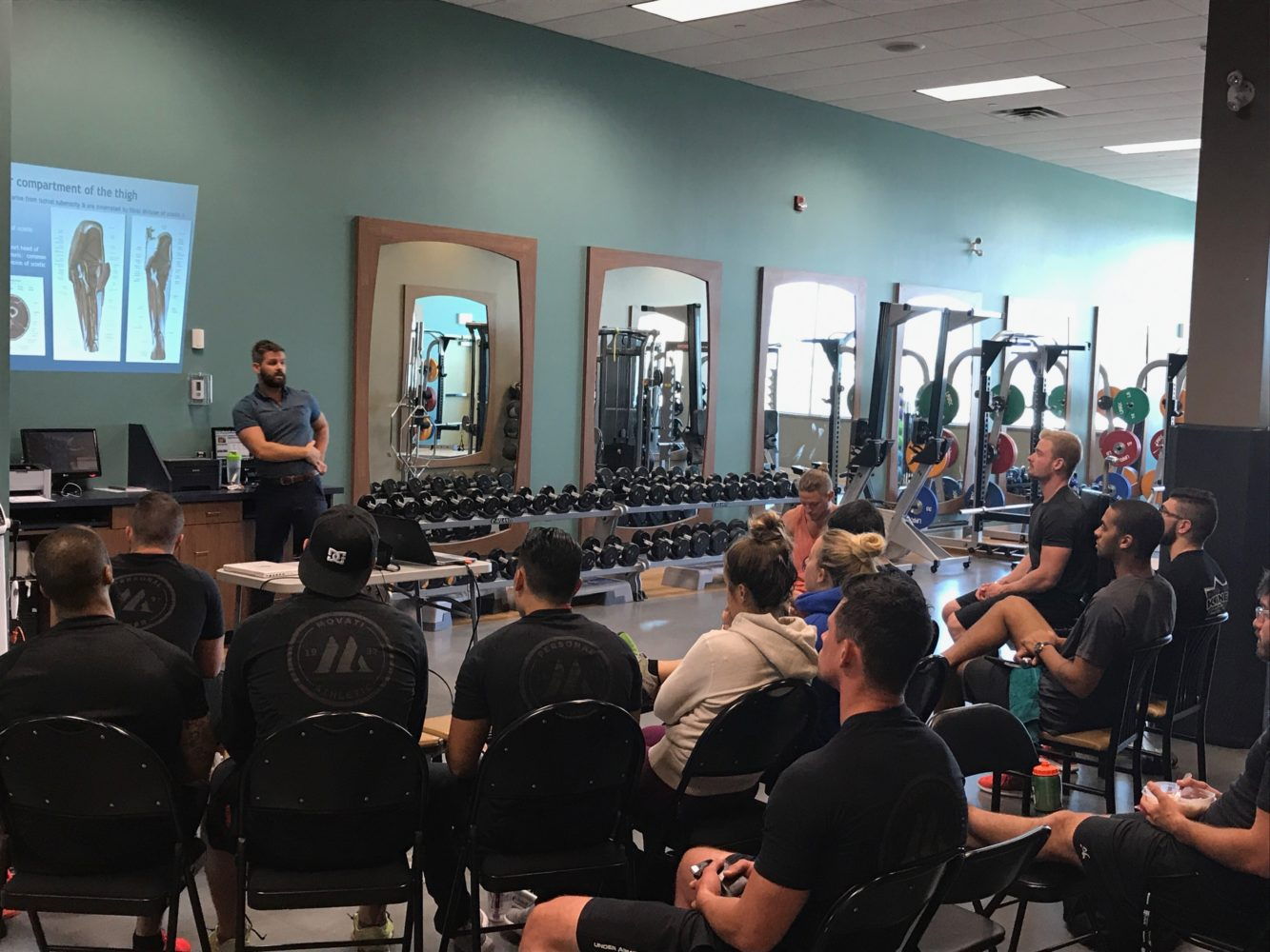 A man holding a seminar in front of a group of people sitting inside of a gym