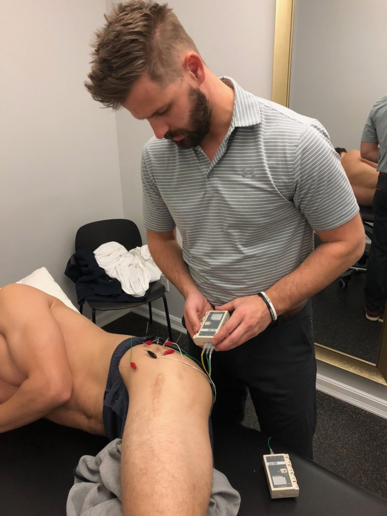 Man holding a device that is connecting to acupuncture needles in another man's upper thigh