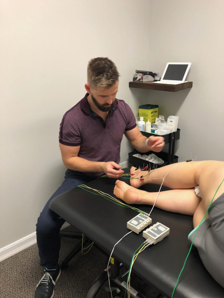 Man inserting acupuncture needles and other devices into another man's foot