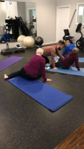 An older woman laying down on a yoga matt inside of an indoor gym